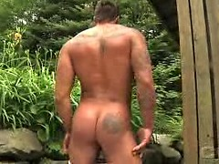 Muscled man stroking hard tool at the nature