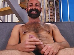 A hairy, Greek guy, bearded, burly and sporting a corking two-hander of thick, juicy meat