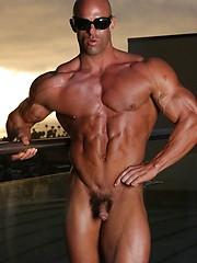 Bald athlete posing on a balcony - Gay porn pics at GayStick.com