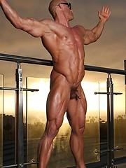 Bald athlete posing on a balcony - Gay porn pics at GayStick.com