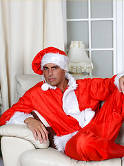 Santa Marcello is dressed in a cheeky outfit and playing with his huge cock - Gay porn pics at GayStick.com