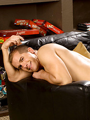 Fresh stud lying on the black leather sofa and showing his cock - Gay porn pics at Gaystick