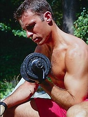 Toned hunk working out outdoors