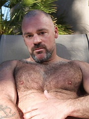 After soaking up some sun, sexy muscle-bear, Bronson Gates heads to a shady area to cool off - Gay porn pics at GayStick.com