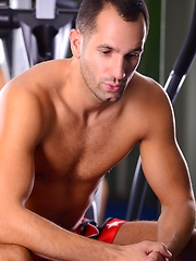 Hunk posing in a gym