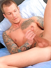 Tattooed dude plays with his hard cock - Gay porn pics at GayStick.com