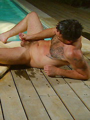 Riley lies on the pool side and plays with his hairy arse - Gay porn pics at GayStick.com